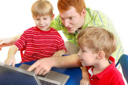 older brother helping younger brothers learn on the internet