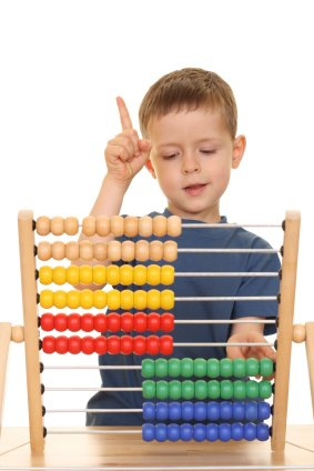 young boy learning to count on an abacus