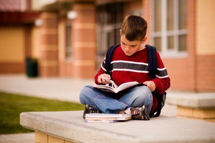 young boy reading outside new school
