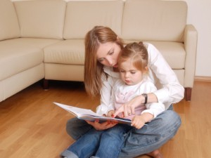 Young mom reading her little daughter on floor